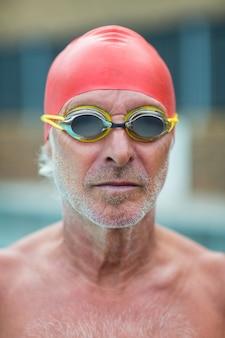 Perto de nadador sênior sem camisa usando óculos de natação