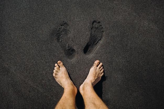 Perto de pegadas masculinas e pés andando na areia preta vulcânica na praia.
