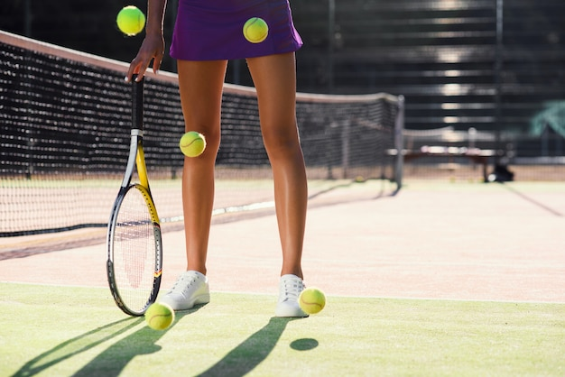 Perto de pernas de mulher deslumbrante com raquete próximo e um monte de bolas de tênis caindo no fundo da quadra ao ar livre. dolly atirou.