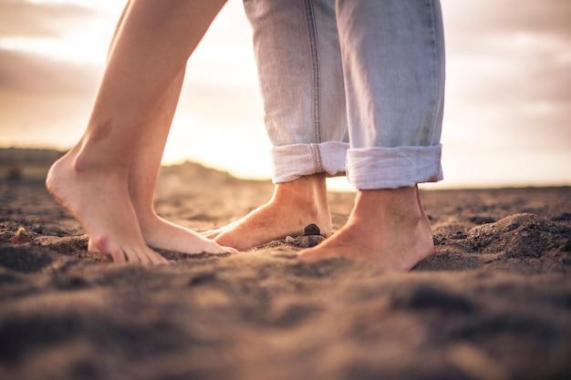 Perto de pés de casal nus para um conceito de amor romântico e romântico - pessoas livres descalças na praia olhando o pôr do sol e curtindo o casal amoroso