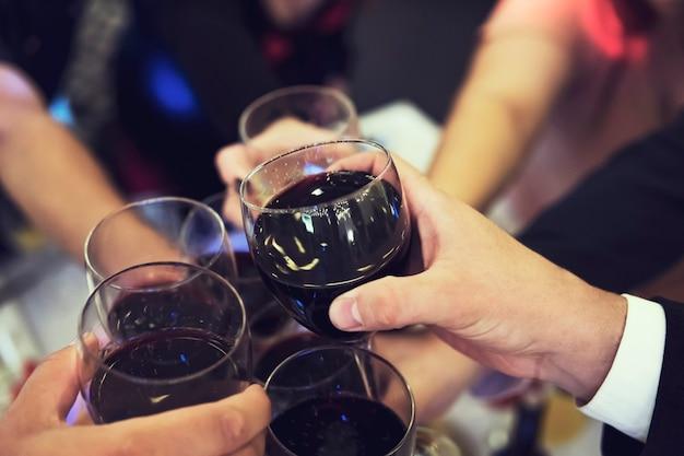 Perto de pessoas tilintando copos acima da mesa reastaurant. brindes em uma noite de banquete. comemoração com bebidas em um jantar. homens e mulheres festejam um evento. um brinde para beber.