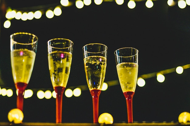 Perto de quatro taças com champanhe na noite do ano novo pronto para celebrá-lo - noite e fundo escuro
