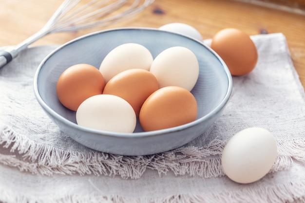 Perto de seis ovos brancos e marrons em um arco azul claro colocado em um pano de prato com uma batedeira de metal no fundo.
