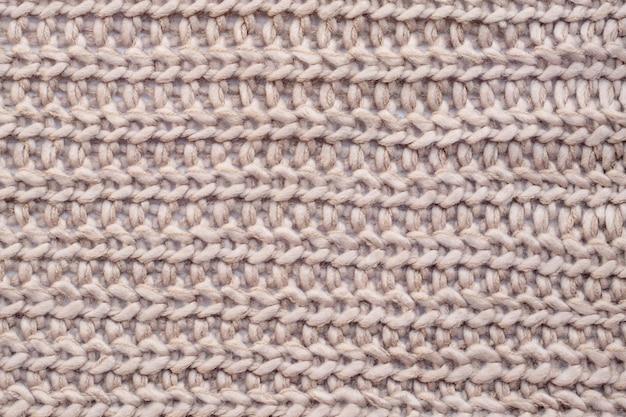 Perto de tecido de malha de lã bege.