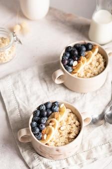 Perto de tigelas com mingau de aveia com mirtilos no café da manhã