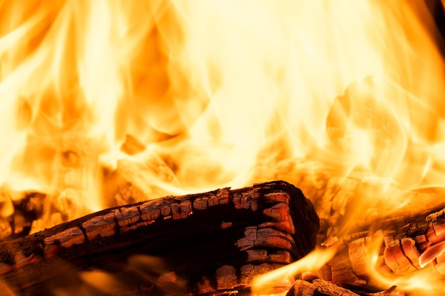 Perto de toras de madeira queimando brilhantemente com chamas quentes amarelas de fogo à noite.