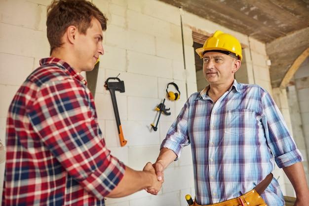 Perto de trabalhadores cooperando e apertando as mãos