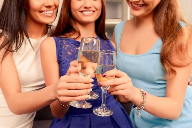 Perto de três mulheres felizes e sorridentes segurando copos com champanhe