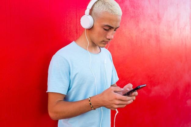 Perto de um adolescente ou milenar usando seu telefone e ouvindo música sozinho ou assistindo vídeos - conceito moderno de cabelo de homem loiro e estilo de vida - parede vermelha no fundo