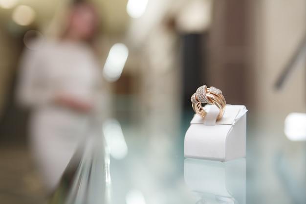 Perto de um anel de ouro com diamantes, mulher fazendo compras em uma joalheria no fundo