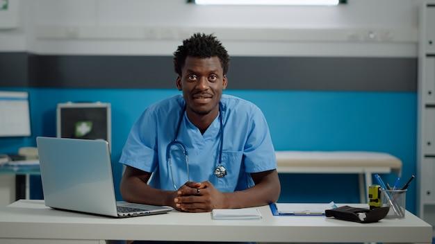 Perto de um assistente médico negro, sorrindo, sentado à mesa