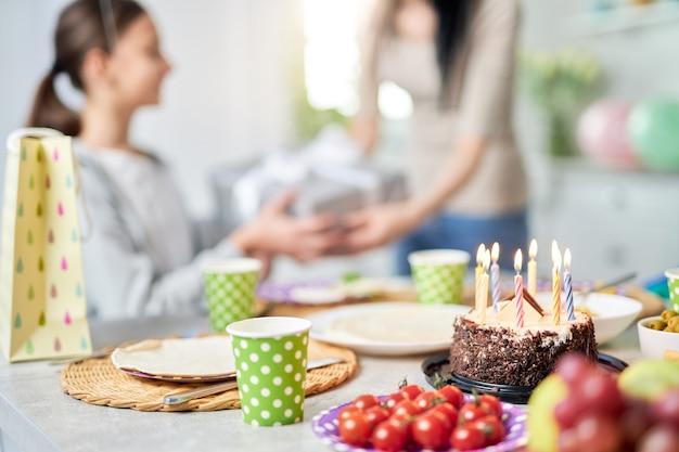 Perto de um bolo de aniversário em cima da mesa. mãe dando um presente para a filha, comemorando o aniversário em segundo plano. foco seletivo