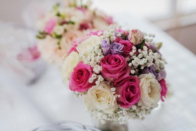 Perto de um buquê de noivas com flores coloridas.