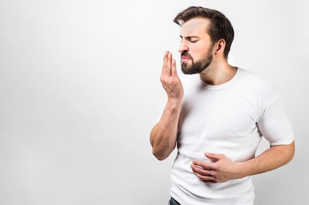 Perto de um cara vestindo uma camisa branca e em pé na frente da parede branca. ele está tentando cheirar a respiração para se certificar de que está tudo bem. isolado na parede branca
