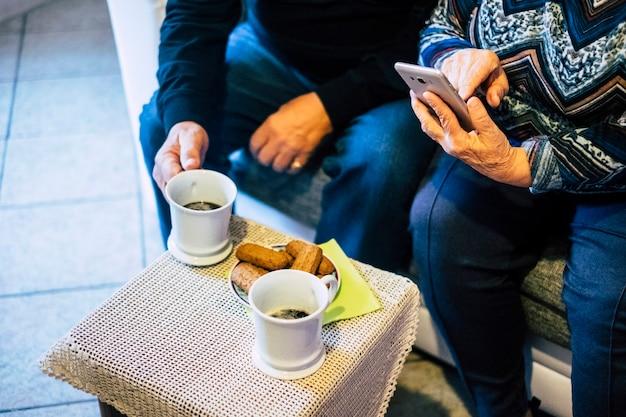 Perto de um casal de idosos caucasianos em casa, aproveitando a hora do chá e fazendo uma ligação com o celular moderno