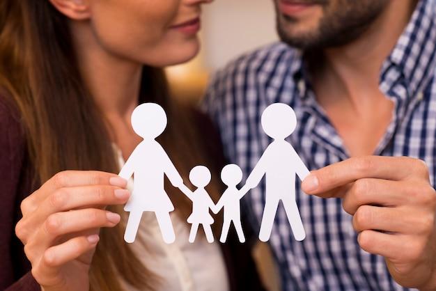 Perto de um casal segurando a corrente de homem de papel de uma família. jovem casal decidindo sobre planejamento familiar. close-up da corrente do homem de papel de uma família. mãos do pai segurando uma família de papel.