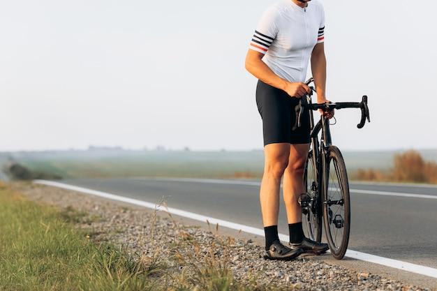 Perto de um ciclista profissional vestido com uma camiseta branca e um short preto consertando uma bicicleta na estrada