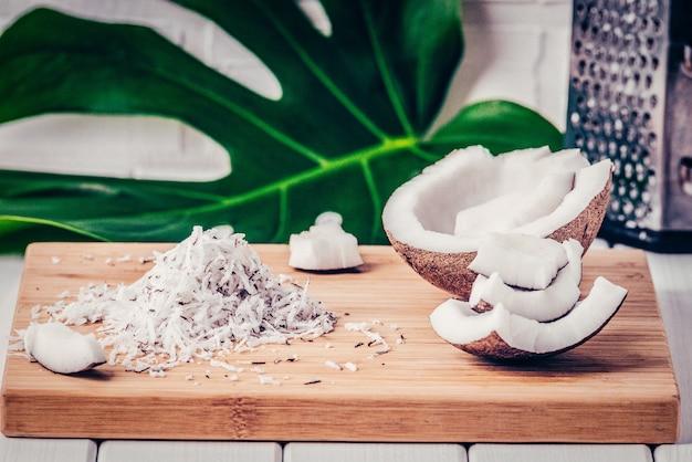 Perto de um coco, o chip de coco, ralador, folha monstera, sobre um fundo de bambu filtro de cores da moda.