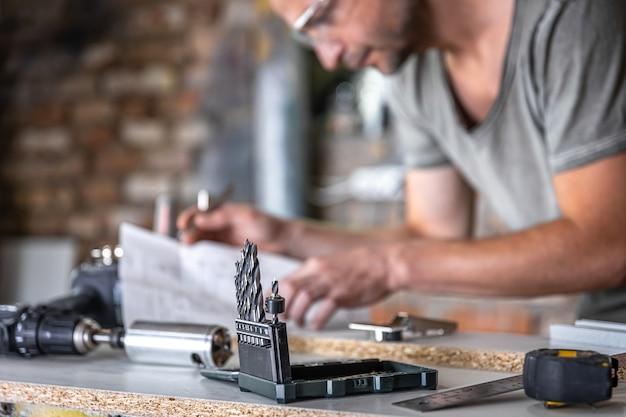 Perto de um conjunto de brocas de madeira em uma mesa de trabalho de um marceneiro em uma oficina.