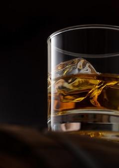 Perto de um copo de whisky de single malte com cubas de gelo em cima de um barril de madeira em fundo preto