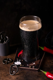 Perto de um copo grande de cerveja escura, cerveja preta forte em um fundo preto com petiscos