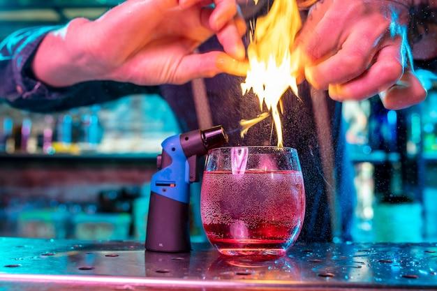 Perto de um coquetel de bebida alcoólica em luz de néon multicolorida com chamas acesas