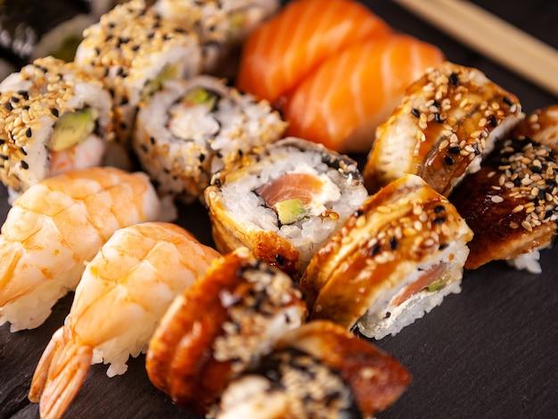 Perto de um delicioso sushi fresco na placa preta