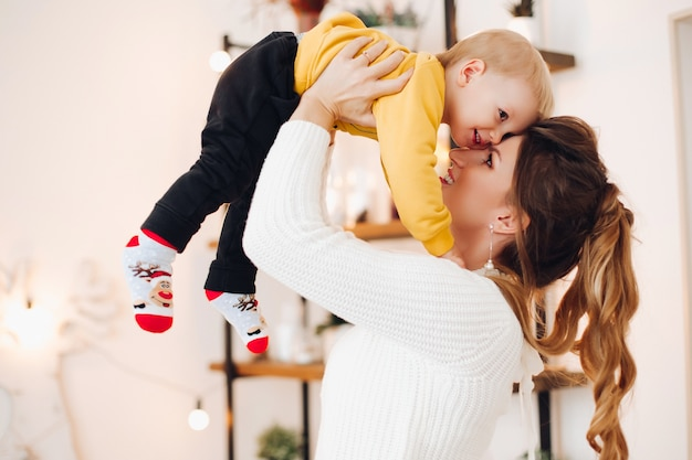 Perto de um garotinho bonito e positivo com uma linda mãe em um estúdio decorado com estilo, olhando um para o outro e brincando