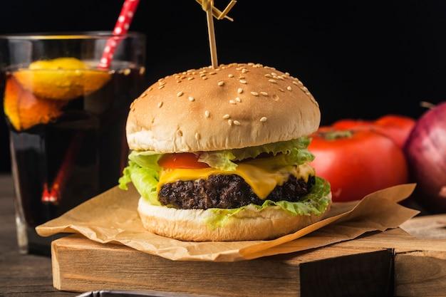 Perto de um hambúrguer de carne caseiro delicioso em uma mesa de madeira.