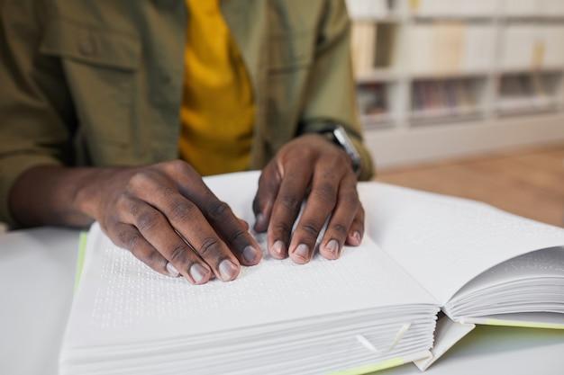 Perto de um homem afro-americano irreconhecível lendo um livro em braille no espaço da cópia da biblioteca da faculdade