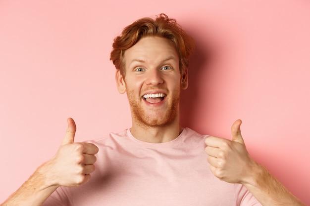 Perto de um homem alegre com cabelo ruivo e barba, mostrando os polegares e sorrindo, dizendo que sim, aprovo um ...