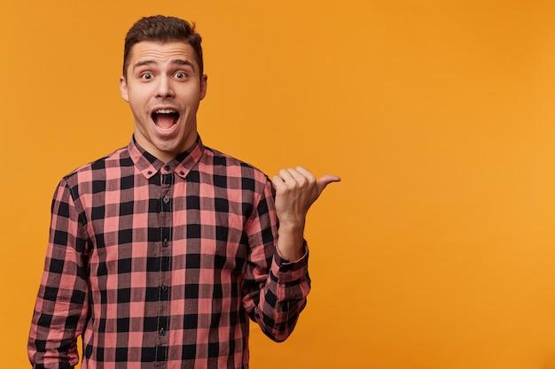 Perto de um homem atraente surpreso e surpreso com uma camisa jeans apontando para o lado direito com o queixo caído