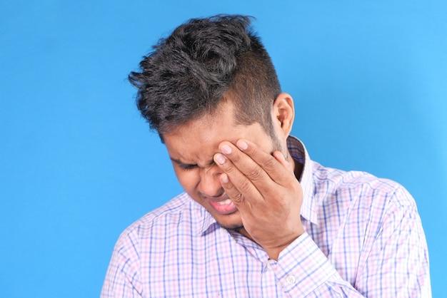 Perto de um homem chateado, sofrendo de fortes dores nos olhos.