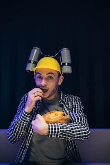 Perto de um homem engraçado com capacete de cerveja na cabeça comendo batatinhas