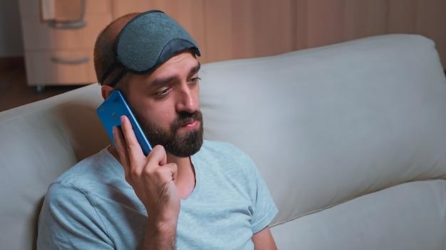 Perto de um homem entediado falando ao telefone com um colega sobre mídia social