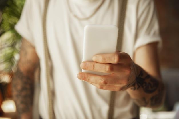 Perto de um homem estiloso usando smartphone, tirando uma selfie