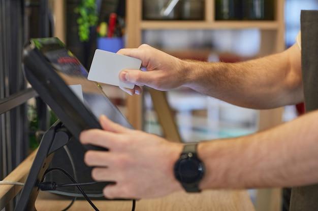 Perto de um homem irreconhecível usando o registro no café enquanto processa pedidos e pagamentos, copie o espaço