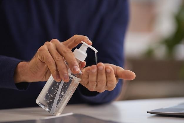 Perto de um homem maduro irreconhecível, usando desinfetante para as mãos enquanto lava as mãos no local de trabalho, copie o espaço