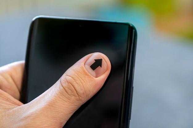Perto de um homem usando um telefone móvel inteligente. a seta na unha aponta para a tela do smartphone. um homem com manicure toca na tela do smartphone.