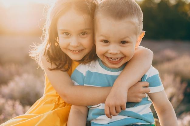 Perto de um irmãozinho fofo e irmã, abraçando e rindo enquanto está sentado em um campo de flores ao pôr do sol.