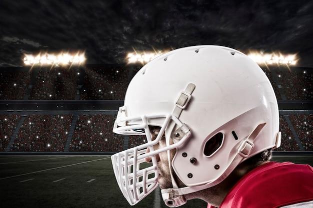 Perto de um jogador de futebol com um uniforme vermelho em um estádio.