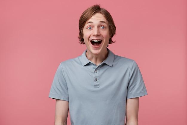 Perto de um jovem animado e espantado com cabelo comprido bem penteado e aparelho nos dentes, usa uma camiseta pólo gritando e se sente feliz surpreso isolado sobre um fundo rosa