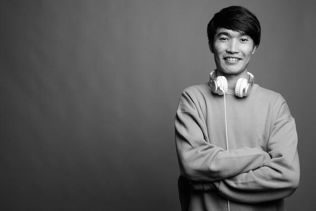 Perto de um jovem asiático usando fones de ouvido