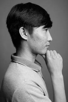 Perto de um jovem asiático vestindo uma camisa pólo cinza