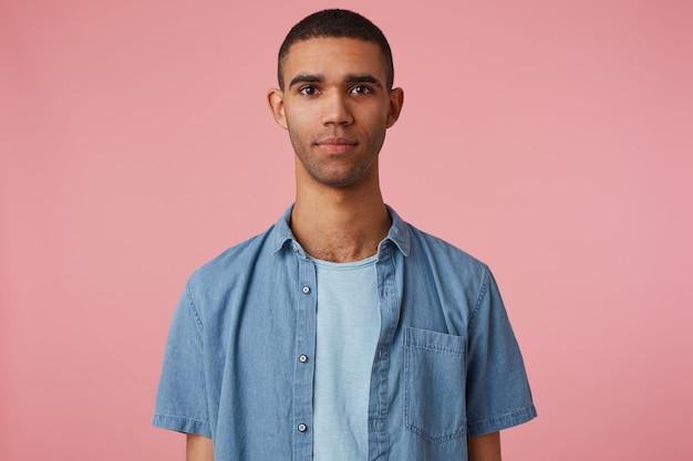 Perto de um jovem atraente de pele escura em uma camisa em branco, olha para a câmera com uma expressão calma, fica sobre um fundo rosa.