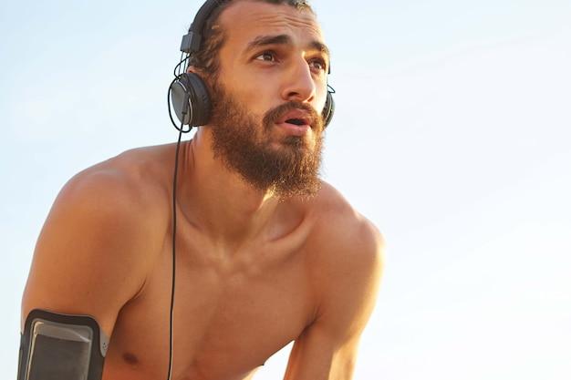 Perto de um jovem barbudo desportivo, descanse depois de se divertir à beira-mar, ouça o mix favorito em fones de ouvido.