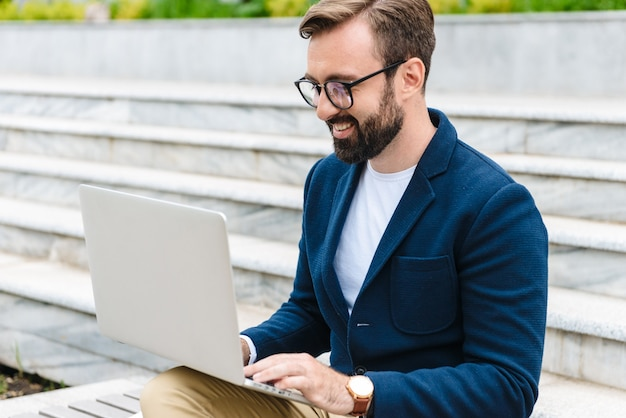 Perto de um jovem barbudo sorridente e bonito, vestindo uma jaqueta, trabalhando no laptop, enquanto está sentado ao ar livre no banco da cidade