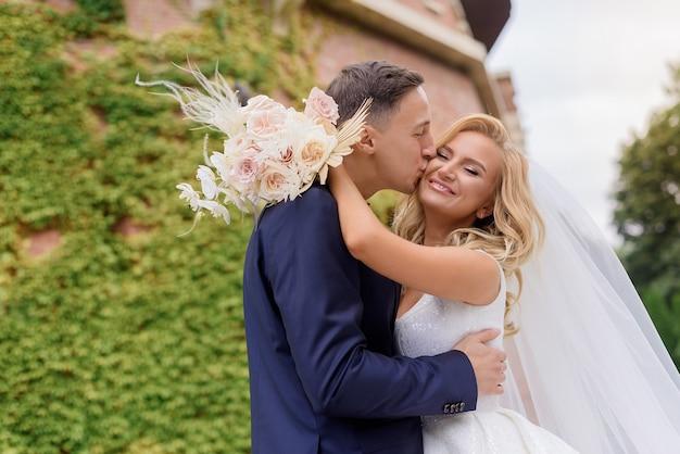 Perto de um jovem casal de noivos vestindo roupas de casamento, em pé ao ar livre, abraçando e sorrindo