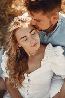 Perto de um jovem casal sentado no campo de trigo. as pessoas se sentam no palheiro no prado e se abraçam.