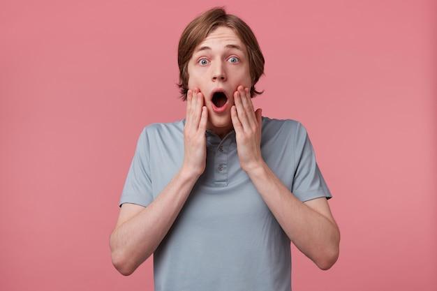 Perto de um jovem com uma expressão espantada e deslumbrada e queixo caído isolado no fundo rosa. guy fica chocado ao ser testemunha do acidente., mãos tocando o rosto